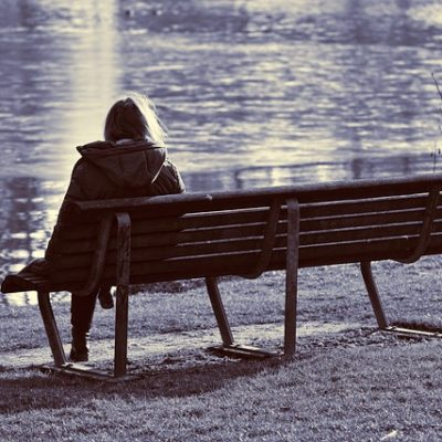 woman sitting alone on a park bench