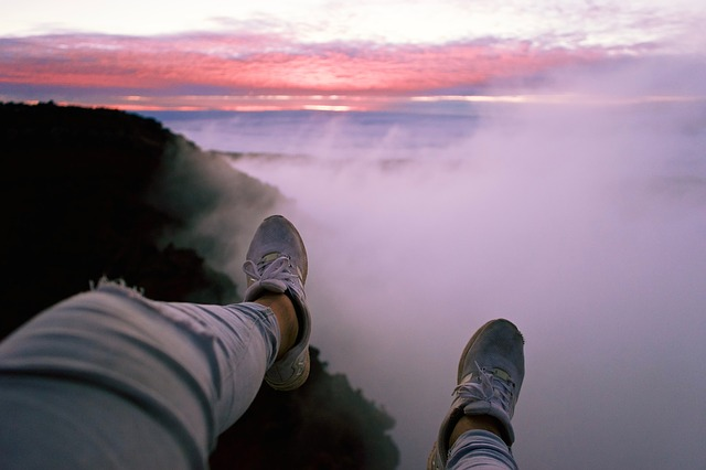persons feet hanging over a cliff